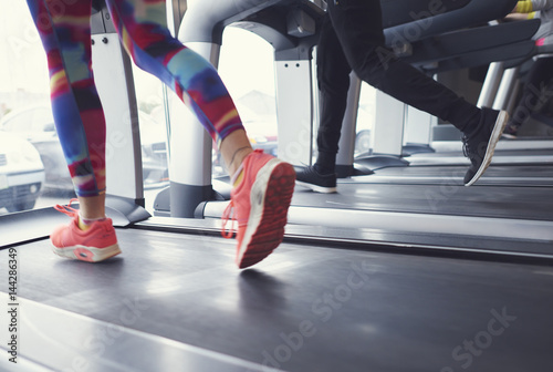Póster Woman and man running on treadmill at gym .