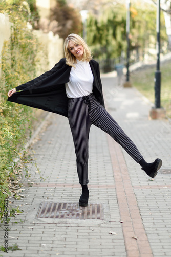 Plakat Beautiful young blonde woman in urban background