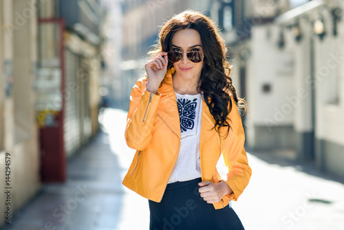 Poster Young brunette woman with sunglasses in urban background