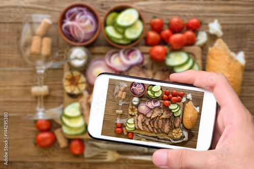 Hands taking photo sliced grilled meat barbecue with smartphone. - 144295380
