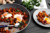 Baked eggs with sausages and potato on wooden table