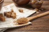 Brown sugar and spoon on wooden background