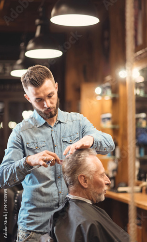 Young barber enjoying working process in the barbershop