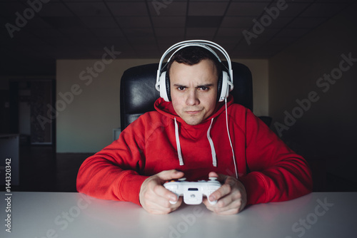 The young man home and playing games on the joystick Poster