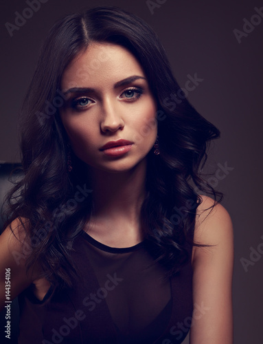 Poster Sexy young makeup model in brown dress and curly hairstyle posing on dark shadow background