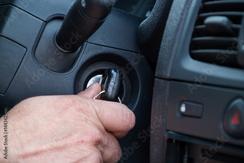 Poster The driver is about to start the car, holds the key in his hand who is in the lo