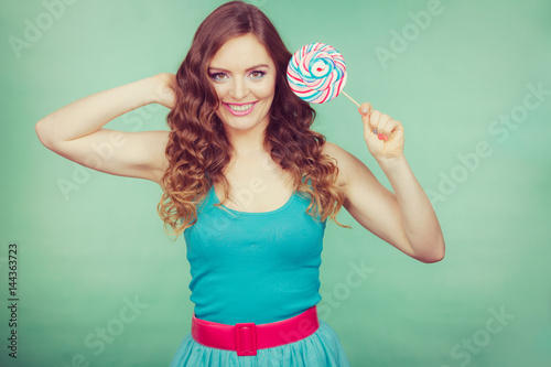 Smiling girl with lollipop candy on teal Poster