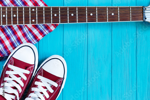 Burgundy sneakers, checkered shirt and guitar fretboard on bright turquoise background