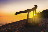 An attractive young woman and man doing yoga on the beach, Seah at sunset