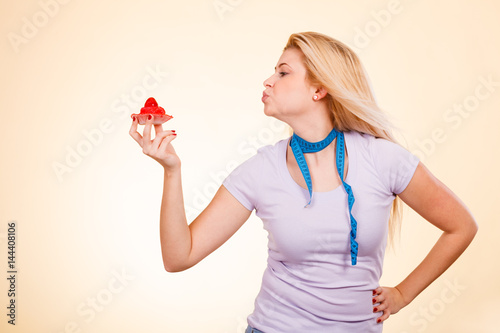 Woman with measuring tape holding sweet cupcake Poster