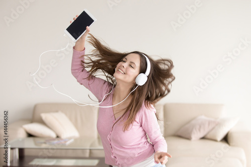 Happy girl listening to music online or radio  via tablet in headphones, teenager music lover enjoying new tracks and songs at home, young lady wearing headset dancing alone, flying hair