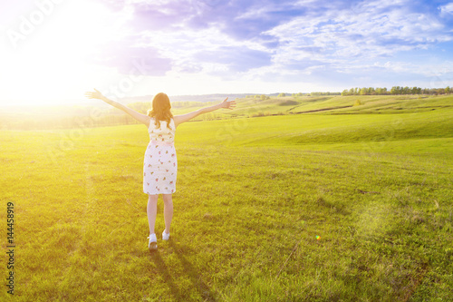 Plakat Happy young woman in white dress in summer green grass field.