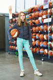 Girl with basketball in sport store