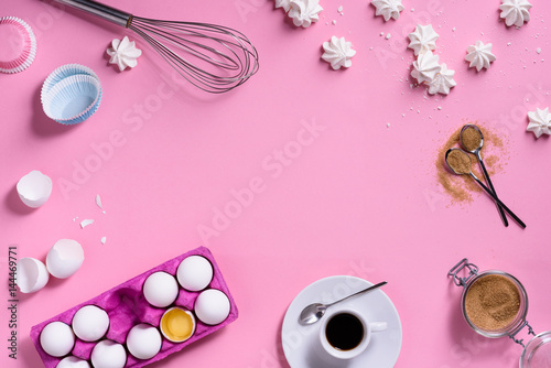 Bakery background frame. Coffee and cooking ingredients - egg, sugar, over pink background. Spring cooking theme. Top view, copy space.