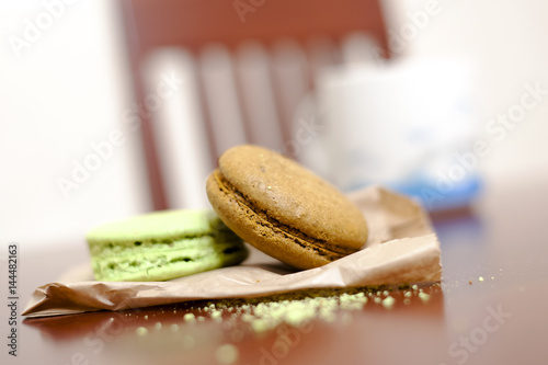 Poster Macaroons on wooden table with cup of coffee in background