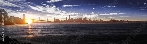 Fototapeta Panorama of downtown San Francisco and the Bay Bridge.  The urban view shows business district buildings and skyscrapers and the pacific ocean.  The image depicts tourism in America.
