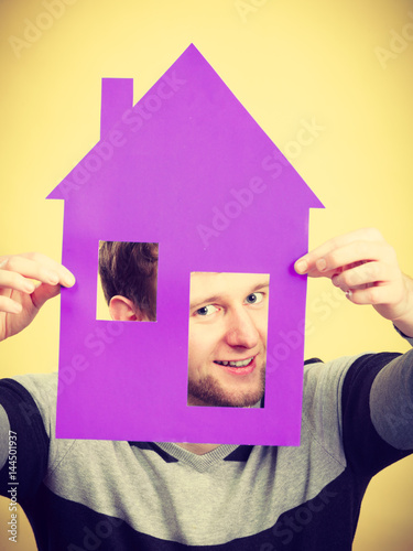 Young man with paper model of house. Poster