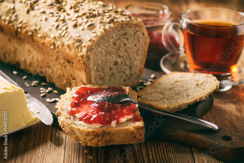 Homemade bread loaf with sunflower seeds on wooden background.