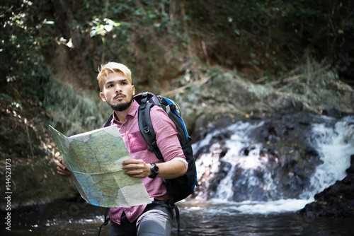 Man traveler with backpack , standing at the waterfall. - 144523173
