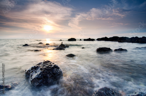 Panel Szklany Stunning sunset moment seascape,soft wave hitting the rock over cloudy sky. infinity focus and long exposure shot