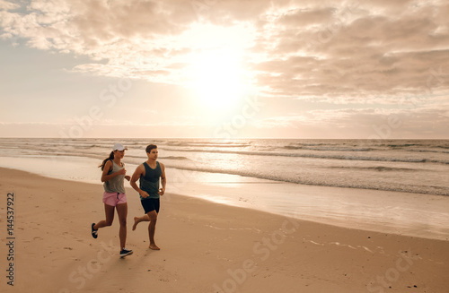 Couple running together on the sea shore