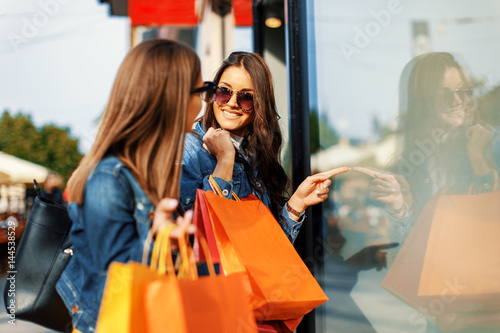 Foto Murales Two young women in shopping looking at shop window in the city