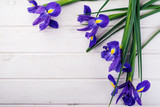 Frame with irises on white wooden background