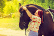 Cowgirl in checkered shirt hugging brown horse