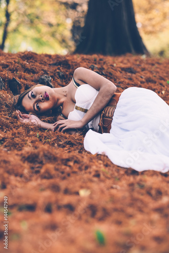 Foto op Plexiglas Draken Portrait of beautiful wiccan girl in the forest, laying on the ground