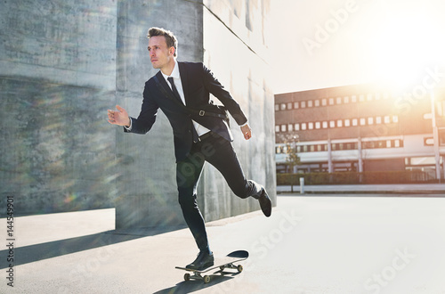 Confident skater wearing suit riding in city