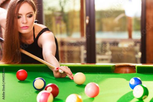 Young woman playing billiard.