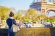 Tourist on the Seine embankment taking photo of the Eiffel tower