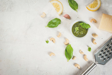 Italian and Mediterranean cuisine. Pesto sauce with ingredients on a white stone table: Parmesan cheese, cashew nuts, butter, lemon, basil. Top view copy space