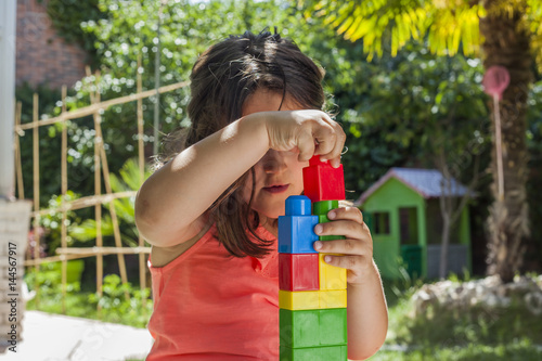 Plagát Portrait girl building with plastic construction toys in the garden
