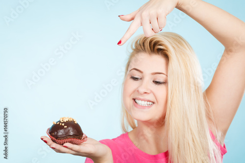 Poster Woman holding chocolate cupcake about to bite