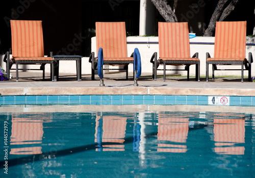 Fotobehang Arizona Orange chairs and their reflections in a pool of a resort in Scottsdale