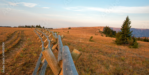 Fotografiet Split Rail Fence at sunrise above Lost Water Canyon in the Pryor Mountains Wild