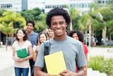 Fototapety Lachender afrikanischer Student mit anderen Stundenden auf dem Campus
