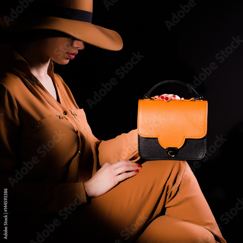 Young brunette woman in a brown suit and fashion styled hat sitting and holding brown-black leather woman handbag on a black background