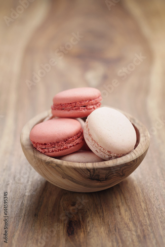 Keuken foto achterwand Macarons pastel colored macarons with strawberry and rose flavour in wood bowl on table