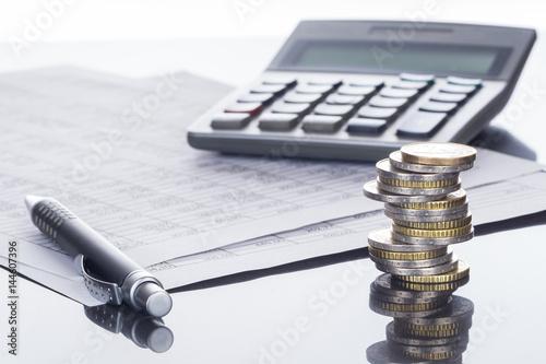 Finanse, stosy monet euro, długopis, arkusze kalkulacyjne i kalkulator, tło
