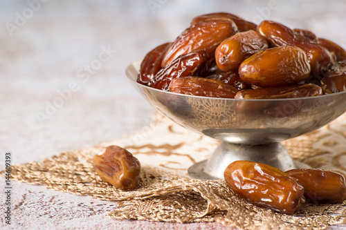 Healthy food. Dry sweet dates in a round metal vase on a napkin.