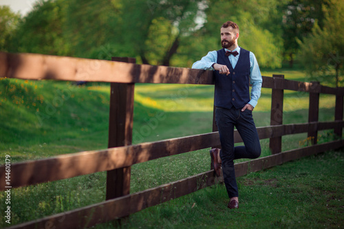 Plakat The bearded groom standing at the wooden fence.
