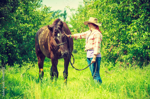 Western woman walking on green meadow with horse Poster