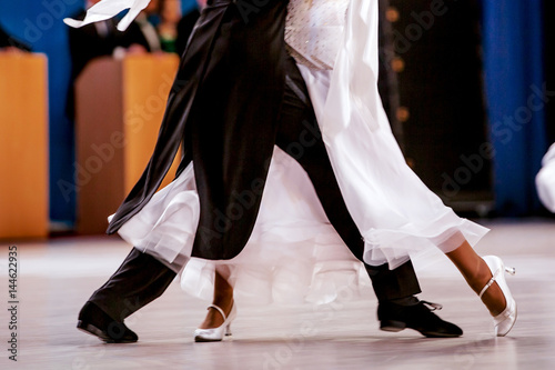 pair athletes dancers ballroom dancing. black tailcoat and white dress - 144622935