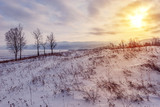 Meadow under the snow by Baikal lake at sunset.