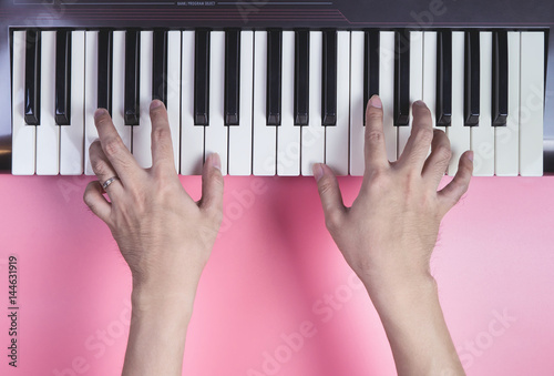 Hand playing Music keyboard on pink background, above view.