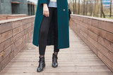 Black ankle boots, black leather bag, warm emerald coat and black trousers. Stylish and fashionable girl on a walk