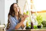 Beautiful happy woman sitting with drinks and healthy green food at home. Vegan meal and detox concept - 144643576