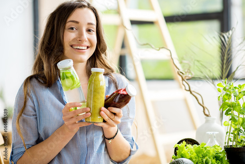 Beautiful happy woman sitting with drinks and healthy green food at home. Vegan meal and detox concept